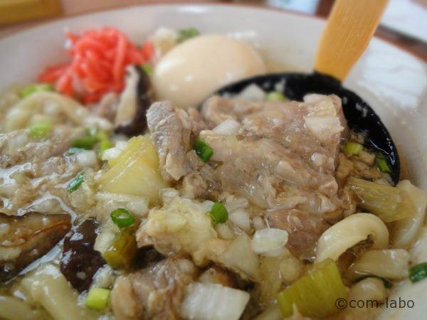 玉ねぎと紅ショウガ、半熟煮卵が浮かぶスープの中でひときわ存在感がある豚ナンコツのかたまり肉