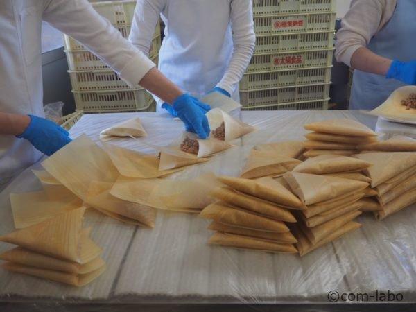 経木に納豆を詰めて梱包している様子